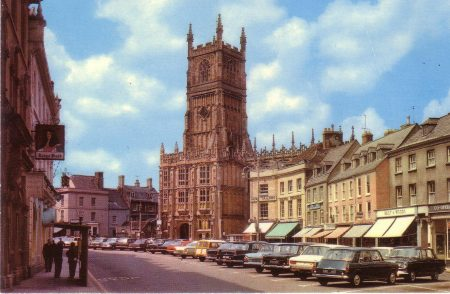 Postcard showing a coloured photograph of Cirencester Parish Church viewed across the Market Place