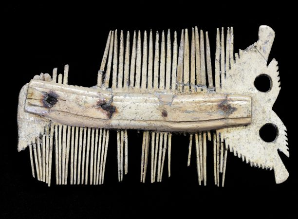 Double-sided bone comb with one end made to look like the face of an owl.