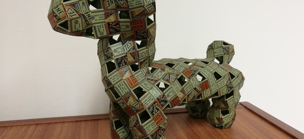 Model of a dog made of interwoven strips of Wills cigarette packets.