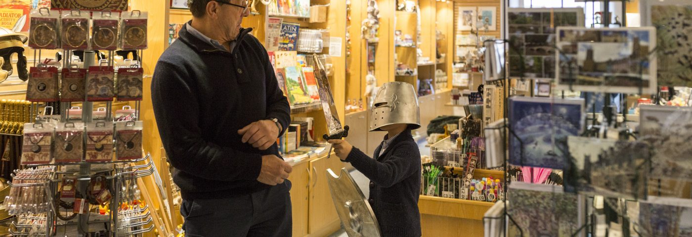 Child wearing helmet and adult in shop